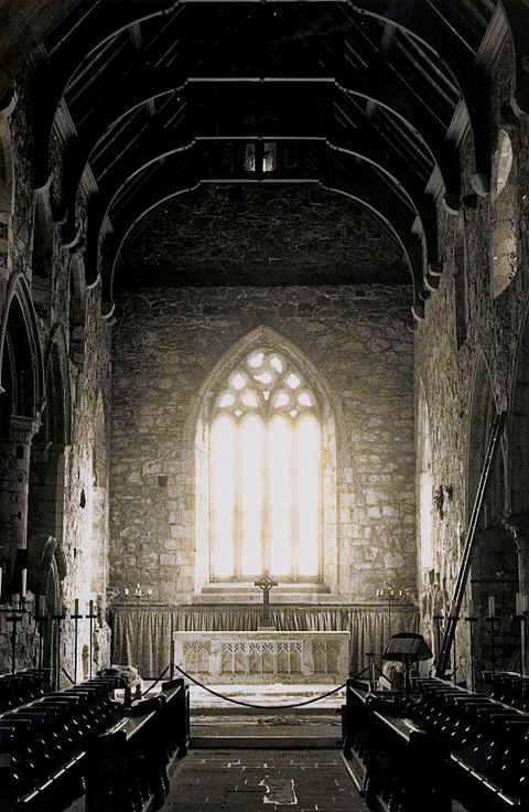 Photo: of the Monastery Chapel on the Scottish Island of Iona, showing the sunlight streaming in through the window.