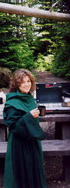 Photo: of Monk Linda holding a cup of cocoa at her Coleman stove in a beautiful wooded area.