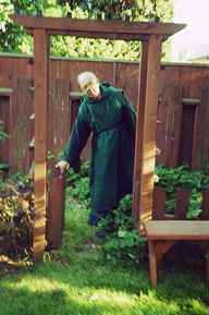 Photo Copyright 2001 S.G.P.  All Rights Reserved.  Photo: of Monk Bob opening a garden gate beneath a trellis in our monastery garden.