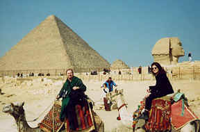 Photo: of Monk Preston and Monk Linda on camels in front of a pyramid and the Great Sphinx.