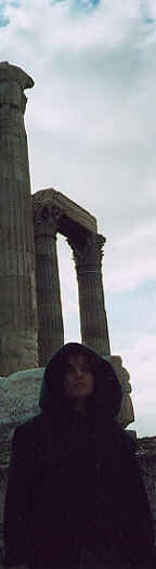 Photo: of Monk Linda, monk's hood up, giant columns of the ruined Temple of Zeus behind her.