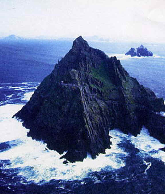 Photo: of Skellig Michael surrounded by the Atlantic Ocean. The ancient stone bee-hive huts are barely seen two-thirds of the way up the rock face.