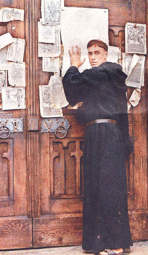 "Photo: Luther nails his 95 theses to the door of Wittenburg Cathedral in the film, ""Luther."""